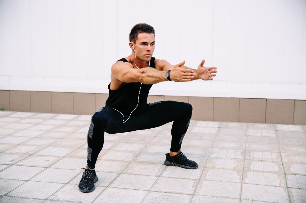Athlete doing squats, outdoors